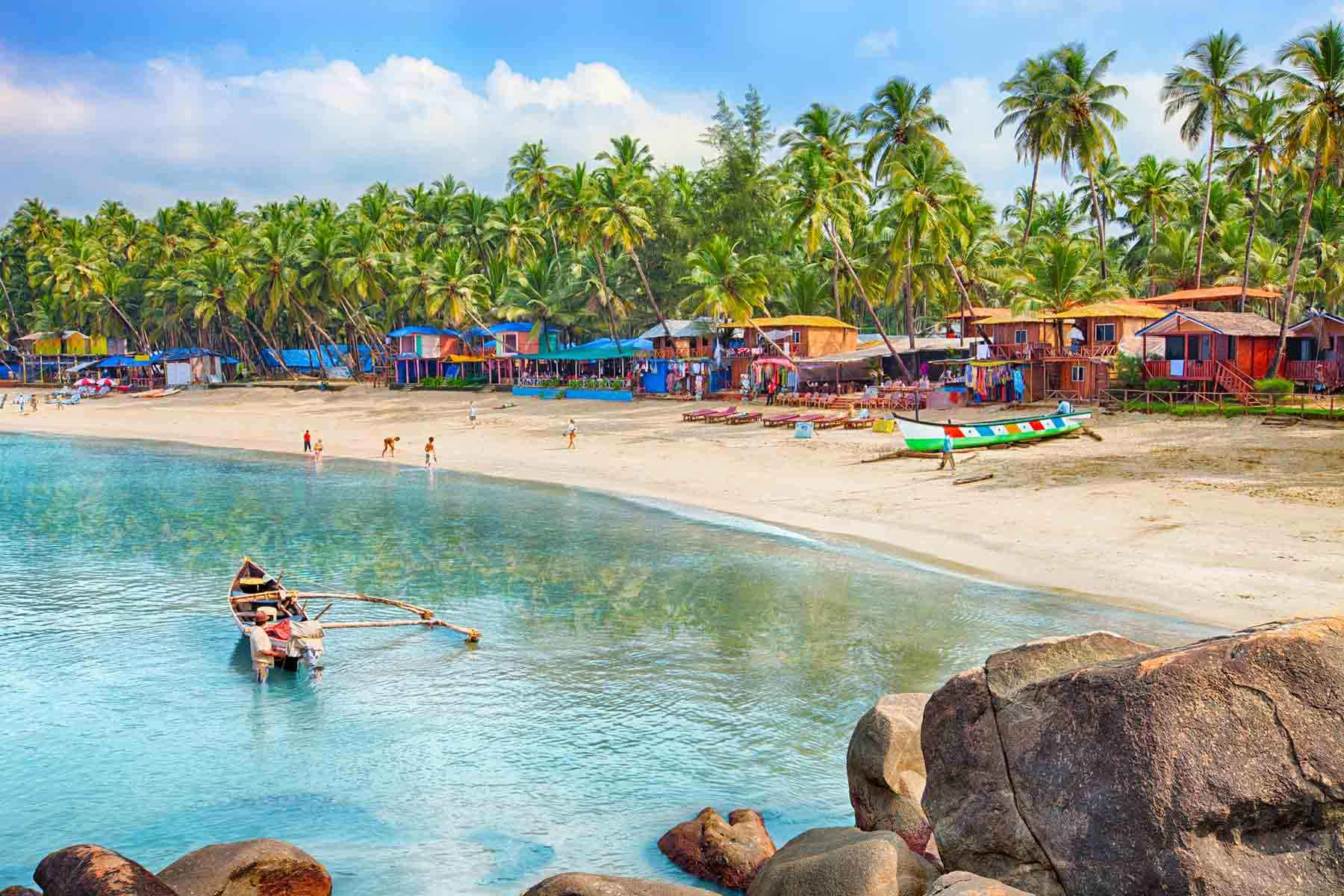 Beautiful Goa province beach in India with fishing boats and stones in the sea